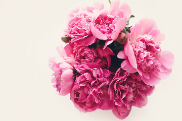 lovely pink peonies bouquet isolated, on rustic white wooden background top view, space for text. floral greeting card mock-up, flat lay. happy mothers day concept. spring image