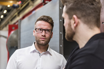 Portrait of businessman looking at employee in factory