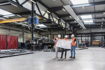 Three men wearing hard hats and safety vests looking at plan on factory shop floor
