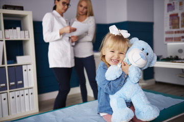 Girl hugging teddy in medical practice with doctor and mother in background