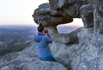 woman photographer takes a sunset among rocks, mountains