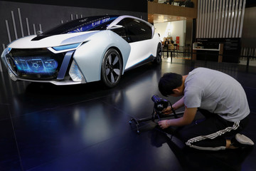 A visitor takes pictures of the Changjiang EV model displayed during a media preview of the Auto China 2018 motor show in Beijing
