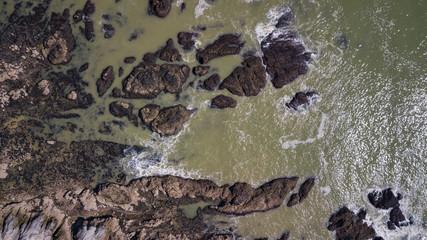 Drone view of waves hitting the rocks at seashore