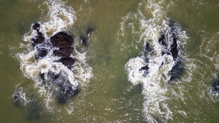Drone view of waves hitting the rocks at seashore