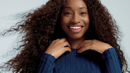 Beauty black mixed race african american woman with long curly hair and perfect smile looking at camera and smiling and wondering and surprised