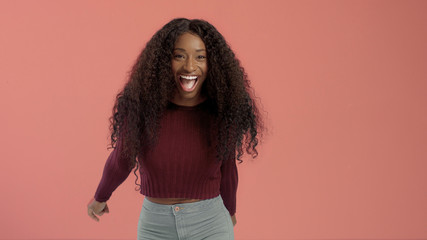 Beauty mixed race african american woman with hair blowed in air smiling at camera dancing On pink background.