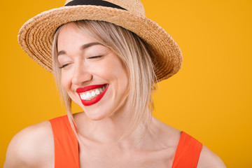 Happy woman laughing with closed eyes. Straw hat. Summer mood. Bright warm colors red and yellow