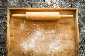 Rolling pin on pastry board sprinkled with flour - kitchen