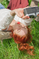 Beautiful young woman relaxing with camera in her hand on garden bench in green grass doing some selfies
