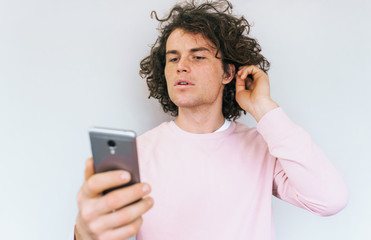 Handsome Caucasian freckled male posing for selfie preparing his curly hairstyle, wearing pink clothes against white studio wall background. People, lifestyle and technology concept.