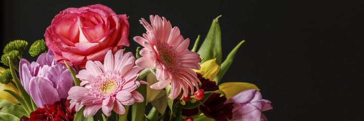 Close-up photo of colorful fresh flowers bouquet for Valentine's Day on dark background