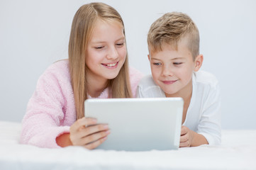 Smiling kids with tablet computer on the bed
