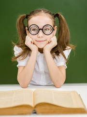 little girl nerd student with open book looking at camera on the background of a school board. concept of poor eyesight