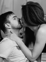 Young beautiful loving couple is embracing on a bed. ntimate image of sensual couple foreplay, kissing passionately. black and white
