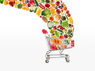 Collage of shopping cart with vegetables and fruits isolated on