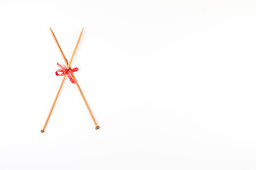 Wooden knitting needles and red and white polka dot ribbon bow on white background