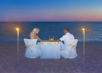Loving couple at romantic dinner with torch flares, candles and luxury decorated table against ocean tropical sandy marvellous sunset beach. Proposal, wedding or honeymoon concept