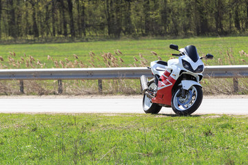 A motorcycle racer stands by the side of an empty road on a sunny day. A lot of green grass on the background. Nobody