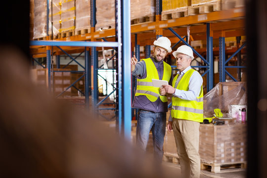 Logistics questions. Nice positive man pointing at the storage shelves while talking to the logistic manager