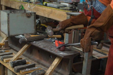The blacksmith skillfully hammers the red hot metal to form a tomahawk head.