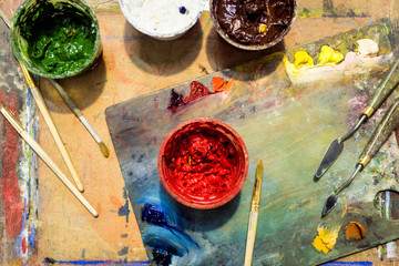 top view of painting brushes, palette and poster paints on wooden table in workshop