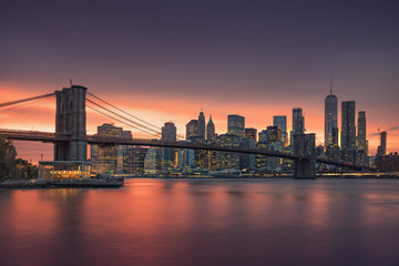 Wall Mural - Famous Brooklyn Bridge in New York City with financial district - downtown Manhattan in background. Sightseeing boat on the East River and beautiful sunset over Jane's Carousel.