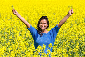 Happy woman arms up in rapeseed field