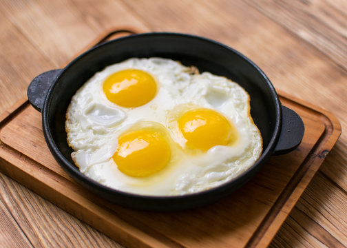 Fried eggs in a frying pan on a wooden background.
