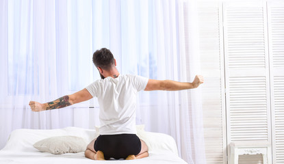 Guy stretching arms, full of energy in morning, rear view. Man in shirt sits on bed, white curtains on background. Macho in underpants stretching, relaxing after nap, rest. Perfect morning concept.