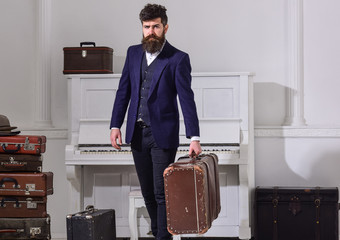 Macho elegant on strict face stands near pile of vintage suitcase, holds suitcase. Baggage delivery concept. Man, traveller with beard and mustache with luggage, luxury white interior background.