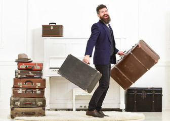 Man with beard and mustache wearing classic suit delivers luggage, luxury white interior background. Butler and service concept. Macho attractive, elegant on smiling face carries vintage suitcases.