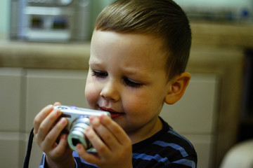 a small boy holds a camera in his hands and stares at the screen