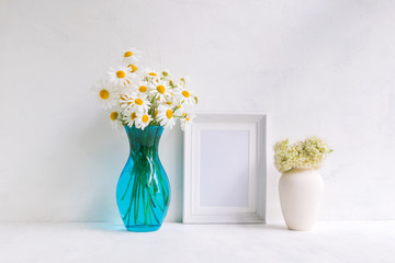 Mockup with a white frame and white daisies in a vase