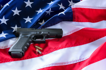 A handgun and bullets on American flag background.
