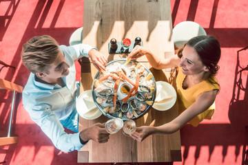 Junges Paar stößt mit Sekt in trendigem Restaurant an