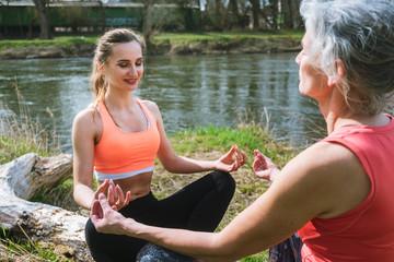Alte und junge Frau beim Yoga am Fluss im Frühling