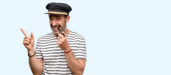 Sailor captain man smoking a tobacco pipe pointing away side with finger isolated over blue background