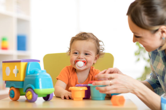 Curly baby boy and woman playing with toys in daycare or kindergarten