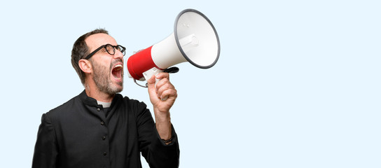 Priest religion man communicates shouting loud holding a megaphone, expressing success and positive concept, idea for marketing or sales isolated over blue background