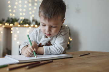 Cute boy drawing on book at table