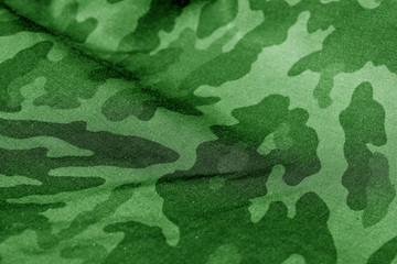 Military uniform pattern with blur effect in green tone.