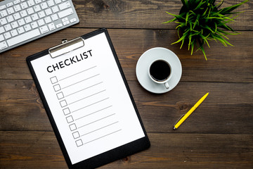 Fototapeta Blank checklist with space for ticks on pad on office desk. Checklist for office worker, manager, businessman, chief on dark wooden background top view