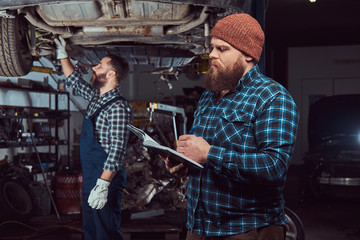 Two bearded brutal mechanics repair a car on a lift in the garage.