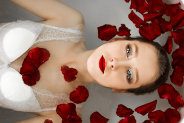 The girl is lying in the bathroom with rose petals. A wellness bath with roses.