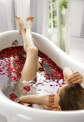A girl in a bath with rose petals. A wellness bath with roses.