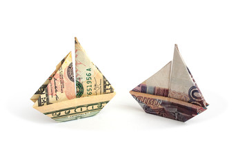 Ruble and dollar bills in the form of sailboats on a white background
