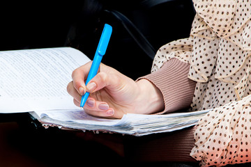 Girl student with a pen in his hand notes important information while preparing to take the exam_