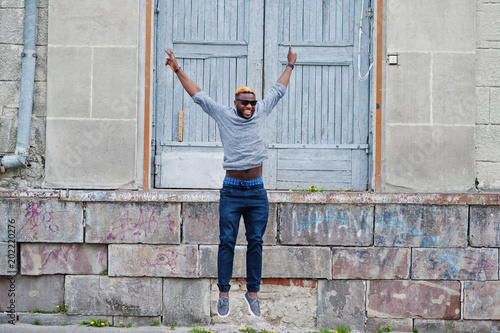 e5510afb0f8 Stylish african american boy on gray sweater and black sunglasses posed on  street. Fashionable black guy jump.