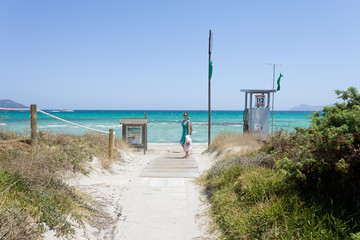 Platja de Muro, Mallorca - A woman walking to the lonely beach of Platja de Muro