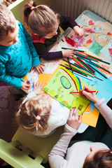 Mom with her little daughters and son together drawing a colorful pictures using pencil crayons